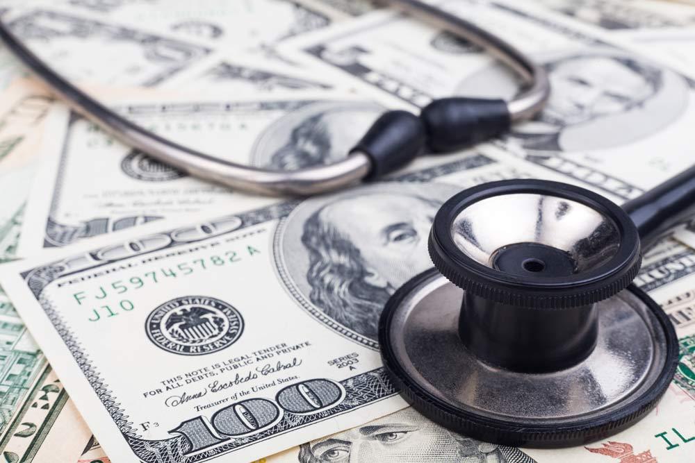 photo of stethoscope on pile of money